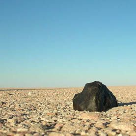 A chrondite meteorite in situ in Rub' al Khali, Saudi Arabia.  Image: Creative Commons | Meteorite Recon