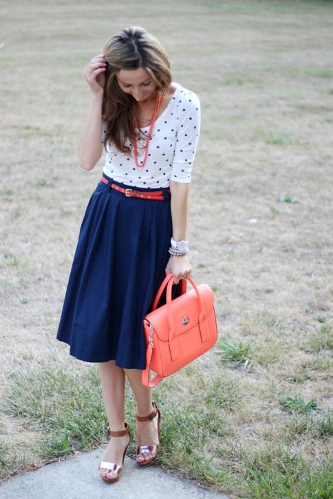 Navy skirt, white polka dot top, coral accessories
