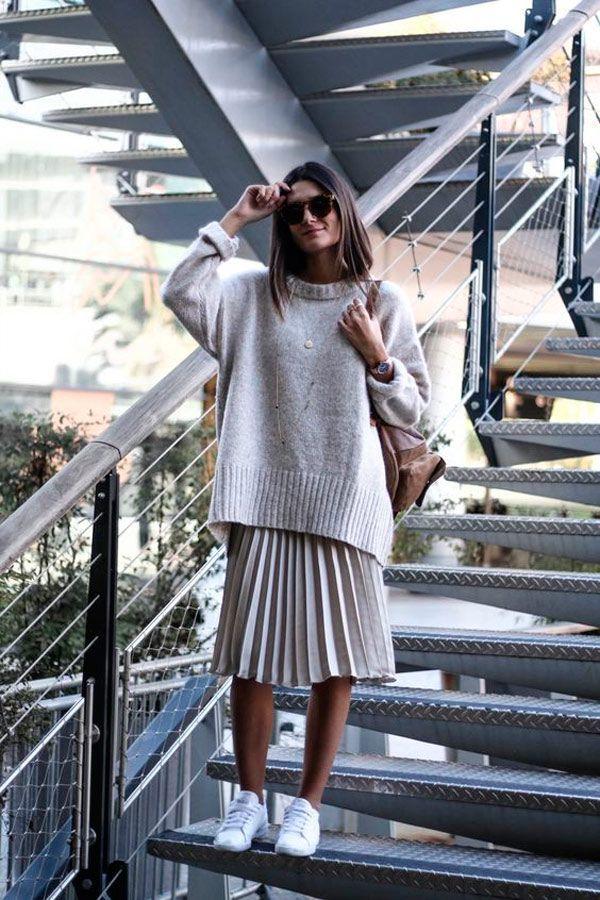 HI-LO-Look mit plissiertem Midirock, übergroßem Sweatshirt und weißen Turnschuhen.