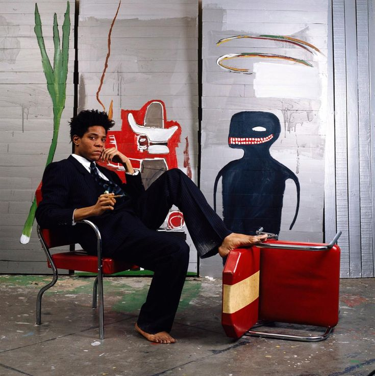 Jean-Michel Basquiat sits surrounded by pieces of his artwork in 1985. The Brooklyn-born artist, who died on August 12, 1988 at the age of 27, has been remembered throughout art history for his use of graffiti, neo-expressionist style of work, and the social commentary communicated through his pieces.