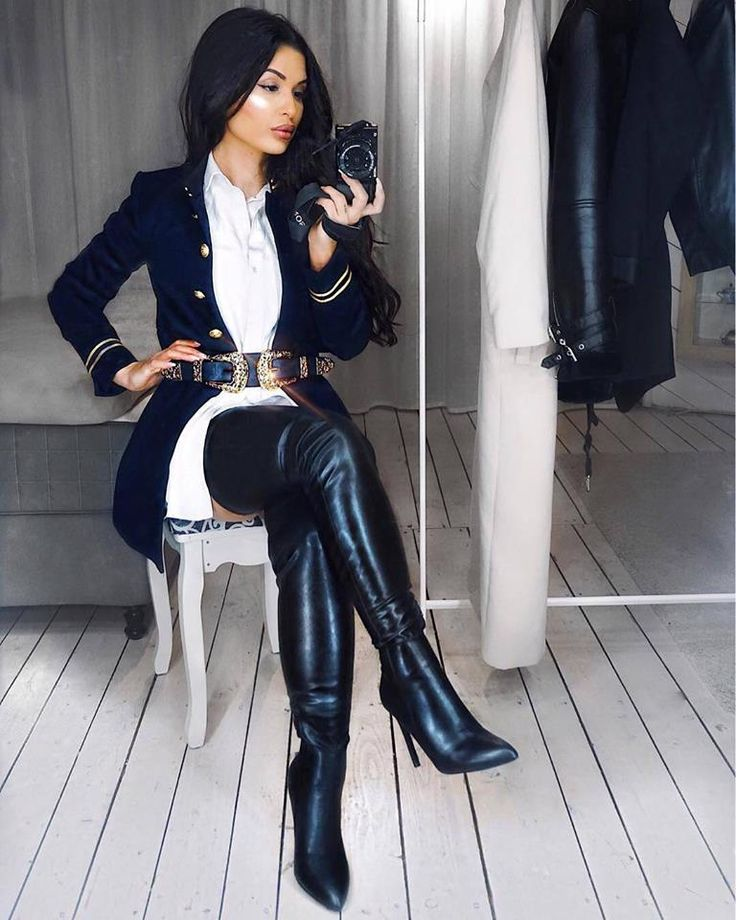 Amateur selfie seated wearing belted military style coat and black leather thigh boots