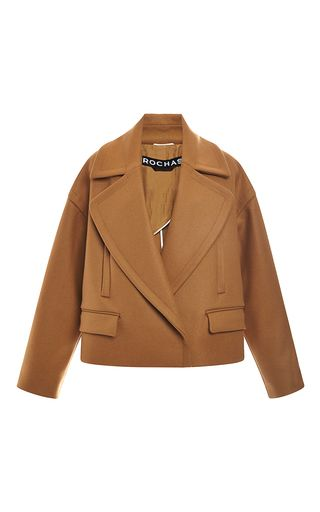 This long sleeve **Rochas** jacket is rendered in a camel colored cashmere and wool blend and features a peak lapel with a pointed collar, two welt pockets and two flap pockets at the front, and a boxy cropped silhouette.