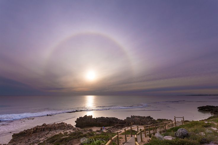 Halo over Trigg Beach in Perth, Western Australia. - Halo is optical phenomenon produced by light interacting with ice crystals suspended in the atmosphere, resulting in a wide variety of colored or white rings, arcs and spots in the sky. This one pictured is called circular halo or 22° halo, which appears as a large ring around the Sun or Moon with a radius of about 22°.
