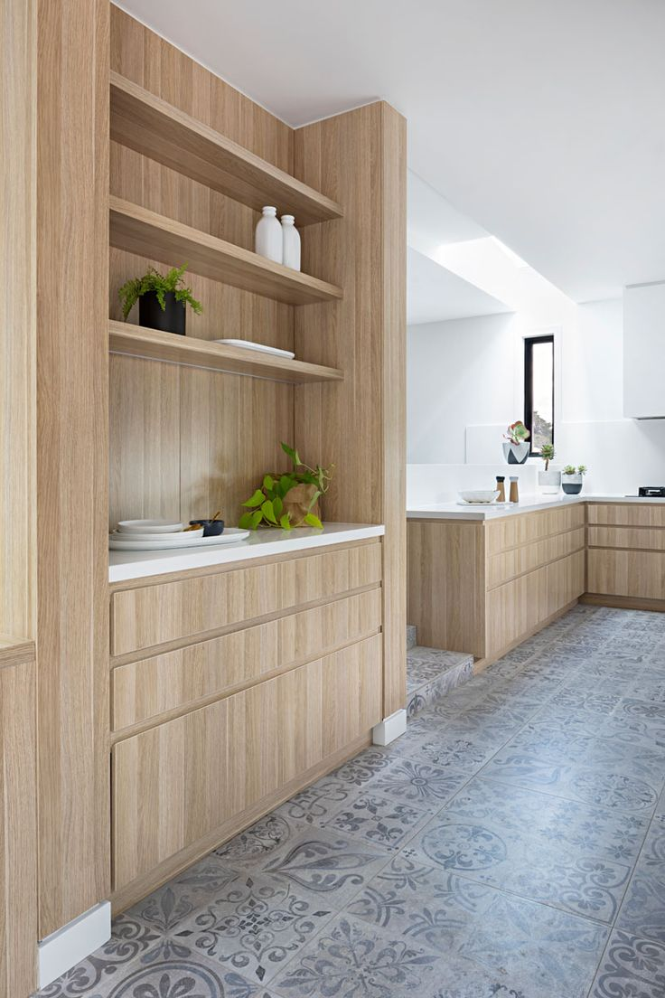 In this light wood kitchen, there's a separate space with built-in cabinetry and open shelves, ideal for extra plates and dishes or as a coffee station.
