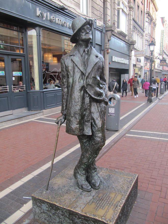 """El escritor dublinés De 1990 realizada por Marjorie Fitzgibbon, está dedicada al novelista irlandés por excelencia. Nació en Dublín en 1882 y retrató gentes y calles de la ciudad de forma magistral en Dublineses y Ulises.  Parece mirar con extrañeza el mundo que le rodea. Algunos se refieren a ella como """"El cabrón del bastón"""", cosa que hubiera encantado al escritor.  La encontraréis subiendo por O´Conell street a la derecha pasado la oficina de correos frente al Spire."""