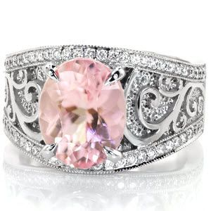 A 2.70 carat rosy hued oval morganite is complimented by glimmering 14K white gold surroundings in this custom design. Contrast is seen again in the high polished spirals curling against a recessed hand stippled background. The flared band is framed by bead set micro pavé diamonds and milgrained edges.