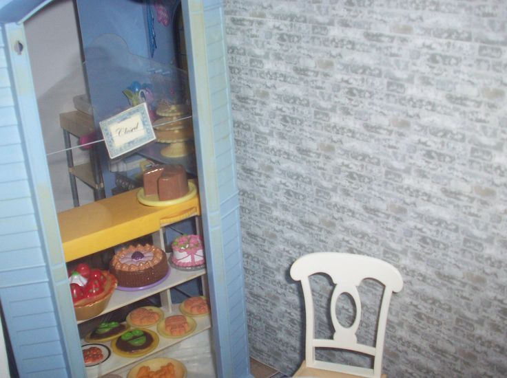 1:6 OOAK dollhouse pet café using part of a Barbie bakery. The faux window is a clear piece of plastic recycled from packaging of a store bought item. An Open/Closed sign was made and added to the window.