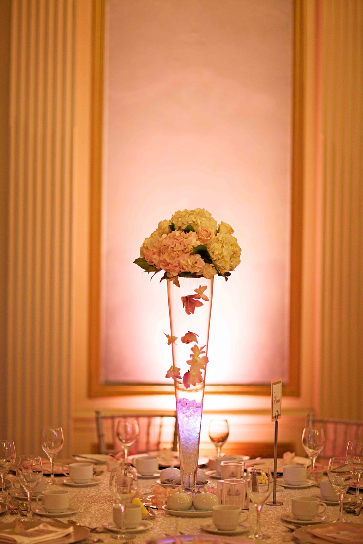 Tall centerpieces in a Pilsner vase topped with Sweet Akito (light pink) roses, white hydrangea, and mini cymbidium orchids; orchids hung inside and outside the vase help draw the eyes down the vase and add multiple layers; Fairmont Palliser Wedding in the Alberta Room; pink wedding décor; Calgary wedding planner and decorator (Photo by Andras Schram Photography)