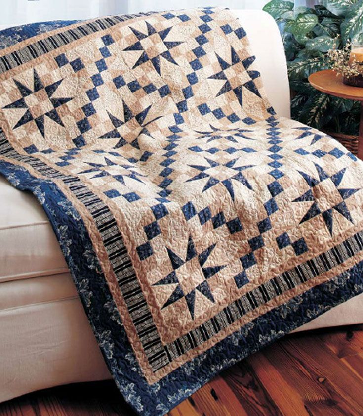 Indigo stars stand out against a background of tan prints, and indigo squares create diagonal chains. Stripe and floral borders provide a perfect finish.