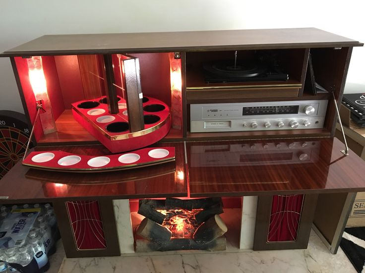 The Phono-Sonic Liquor Cabinet-Stereo with fireplace.  It has a 8-track player (yes it does), a turntable that has three speeds (33/45/78), a radio, a bar, and an artificial fireplace.  Many call it:  Koronette Console Stereo Bar Fireplace. Produced around the 70's era.  They were made in what was referred to as East Germany at the time and brought to the US.  Speakers are hidden behind the doors with red velvet.