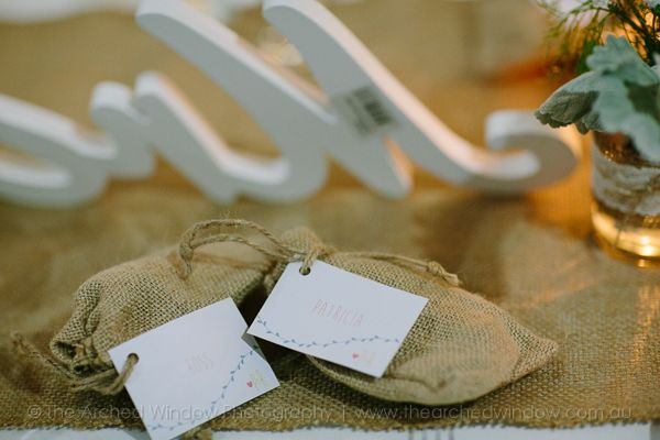 Hessian wedding favours against a hessian table runner at a wedding reception. Photography by The Arched Window.