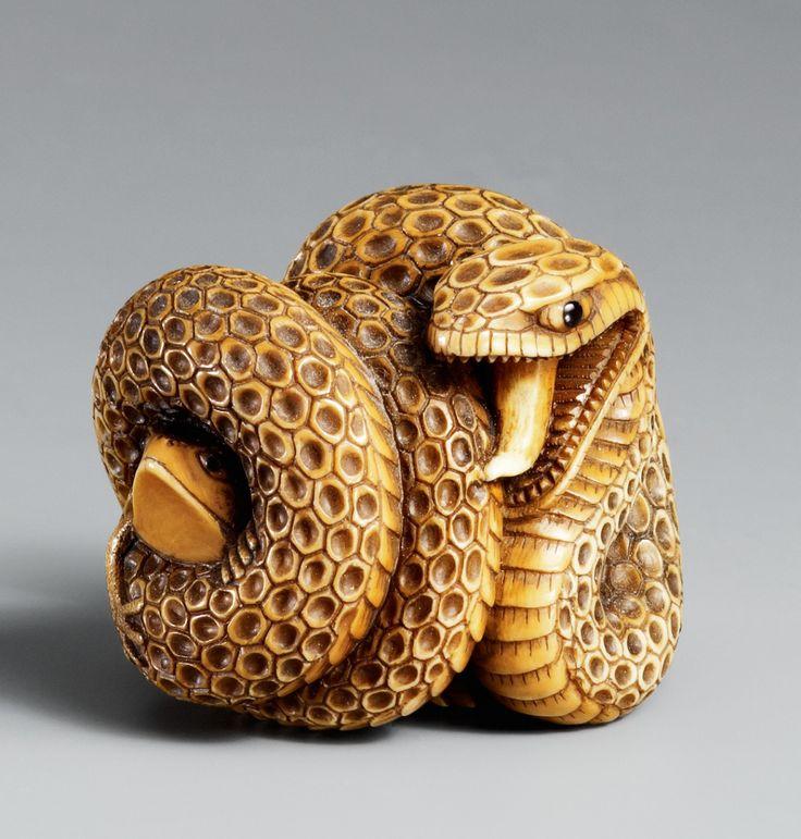 Schlange und Frosch. Elfenbein. 20. Jh.  Die große Schlange mit mehrfach gewundenem Körper, geöffnetem Maul und langer sichtbarer Zunge, aus einer der Windungen schaut ein Frosch hervor, die Pupillen der Tiere aus schwarzem Glas.
