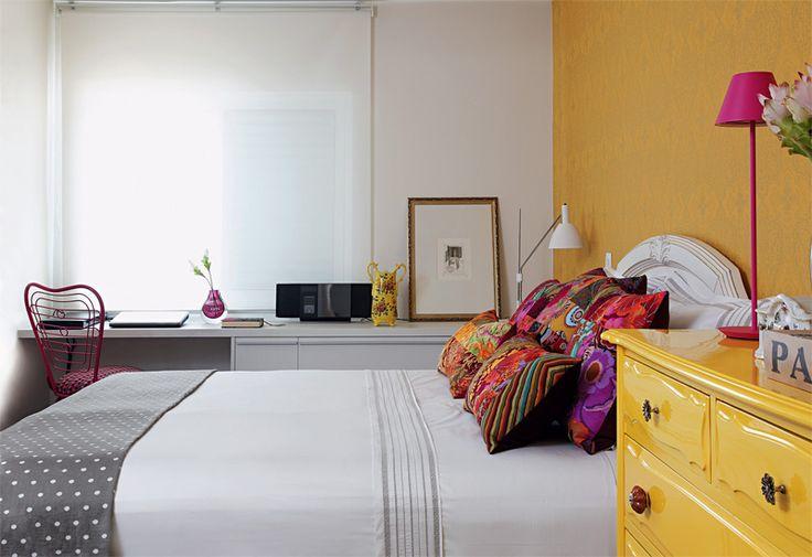 Papel de parede (Espaço Paper) e cômoda (Estúdio Glória) se cobrem de amarelo no quarto do casal.
