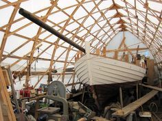 """Proving that everything is bigger in America, Matthew Billey sent us a photo of his boat shed in Gloucester, Massachusetts. He writes: """"Here's a pic of my """"cathedral"""" boat shed. Built from lumber yard 1"""" x 3"""" strapping, formed into bow-shaped rafters, this shed perfectly complements my scratch-built Danish double-ended sailboat, under construction. I've often been told my shed looks like an upside-down boat."""""""