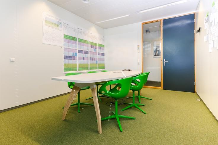 In de groene kamer kleuren de Rin chairs van Fritz Hansen perfect bij de Desso vloerbedekking