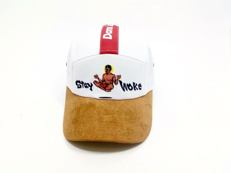 "Dans Le Groove Presents: Stay Woke * White 5-Panel Cap * Tan Curved Suede Brim * Adjustable Brown Leather Back Strap * ""Stay Woke"" Laser Embroidery  * ""Dans Le Groove"" Satin Label * One Size Fits All Deriving from ""Stay Awake"", to Stay Woke is to keep informed of the shitstorm going on around you in times of turmoil and conflict, specifically on occasions when media channels are being flooded with heavily filtered one sided ""Opinion News""."