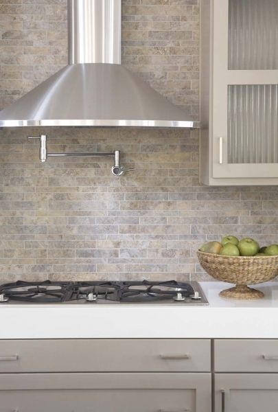 Gorgeous modern kitchen design with taupey gray shaker kitchen cabinets with white quartz countertops and tumbled stones backplash
