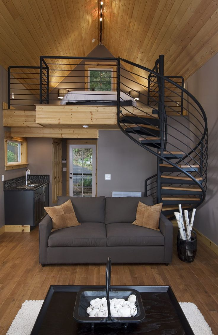 Stylish tiny house with spiral staircase, high wooden ceiling, and wooden  floors.