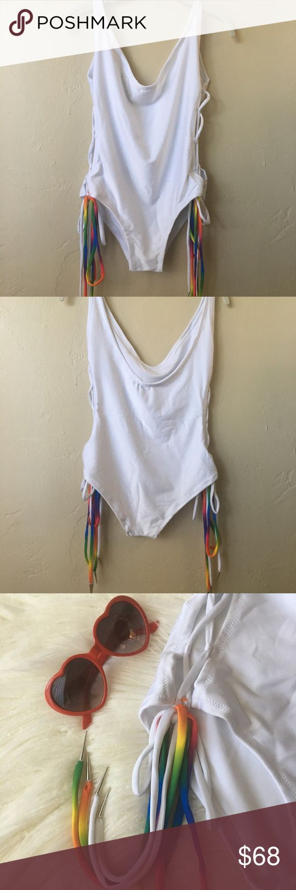 "🆕 Rainbow Tassel 🌈 One Piece Swimsuit NWT Rainbow Tassel Ice Queen Swimsuit from Stardust. One piece, size Medium. Open sides with white and rainbow colored tassels on each side. Tassels have metal tapered aglets on the ends 🌈 No built in support, but would easily fit up to a C-cup. Laid flat measures 14"" across chest, 19"" shoulder to hip, with 10"" leg openings. Scoop neck in front and back 🌈 Model picture shows lavender but this suit is bright white. Does not go sheer! Perfect for pool…"