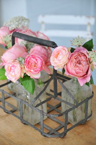 Roses and vintage bottles. Cute centerpieces for a rustic or vintage inspired wedding