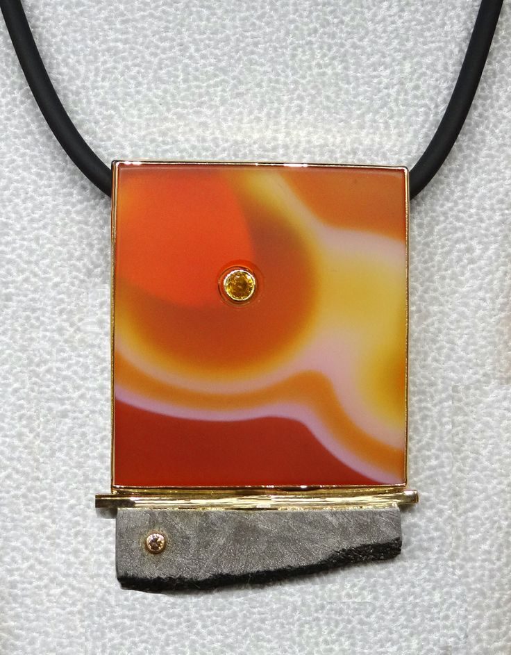 Bezel set Agate with an orange sapphire bezel set in the Agate at the top and meteorite slice with a bezel set natural colored diamond at the bottom by Patrick Murphy.
