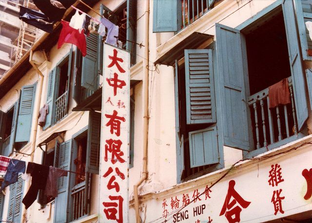 Old Singapore shophouses with clothes on bamboo poles set out to dry in the sun