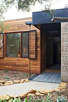 14 Modern Homes That Use Rain Chains To Divert Water // A chunky black chain carries rain water into a bed of rock at the front door of this home creating an industrial look as you walk in.