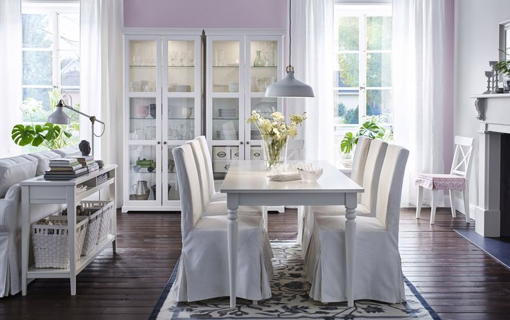A large dining room with a white dining table and six chairs covered in white cotton. Completed with two high glass-door cabinets and a console table.