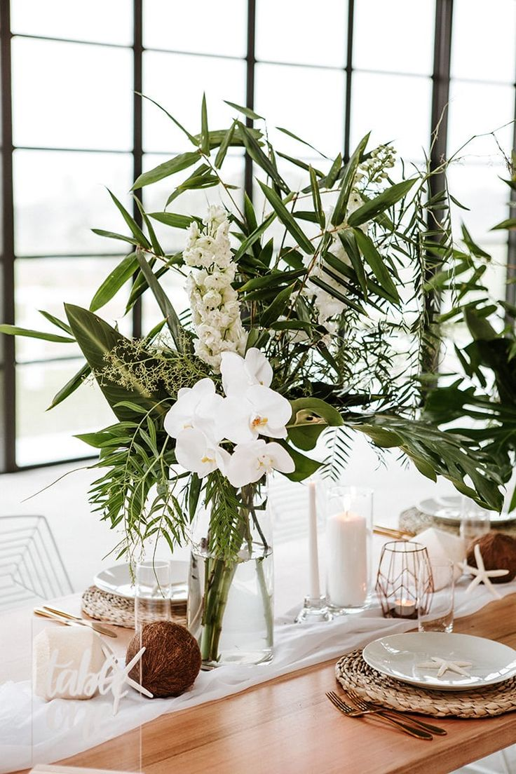 Coastal barn wedding reception table with tropical greenery, white orchids, coconuts and starfish   Red Berry Photography
