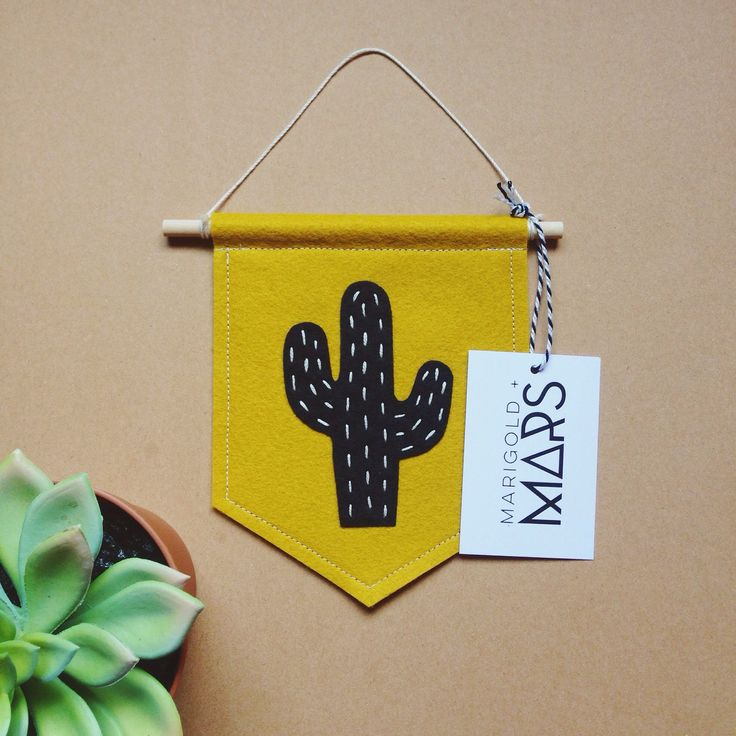 "Bring a bit of the Wild West to your walls with these felt cactus banners. Each mini banner is made from vibrant wool-blend felt and features a hand-embroidered cactus.  Banners measure approximately 4.5"" x 6"".Banners are ready to ship.PLEASE NOTE: Each cactus banner is handcrafted individually and might vary slightly from what's pictured…"