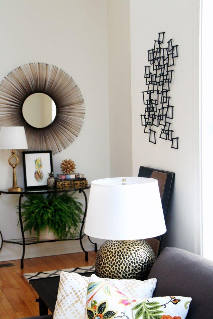 dunkle couch, helle blumenkissen, pflanzen