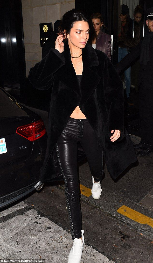 Model behaviour:She flaunted her enviably toned abs in a simple ribbed black crop top and slung a plush long-line fur coat over the top