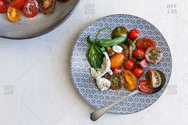 Tomato salad on patterned plate;   tomatos, mediterranean, basil, caprese, salad, cherry tomatoes, exotic, olive oil,