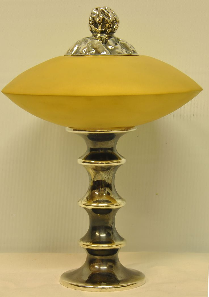 Decorate your bathroom with grace and elegance. This bath salts container integrates your bathroom décor with the sophistication of gold and silver. It is uniquely shaped like a flying saucer, made of glided metal, with a silver lid, a knob, and a dragon mask on the inside. All these elements, together with a lathed silver base, make this accessory utterly unique.