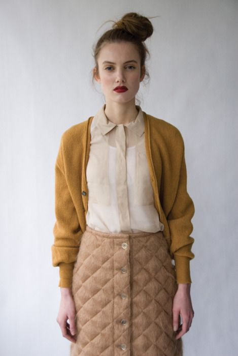 Not a fan of the quilted skirt but I love the sheer blouse paired with the mustard cardigan.