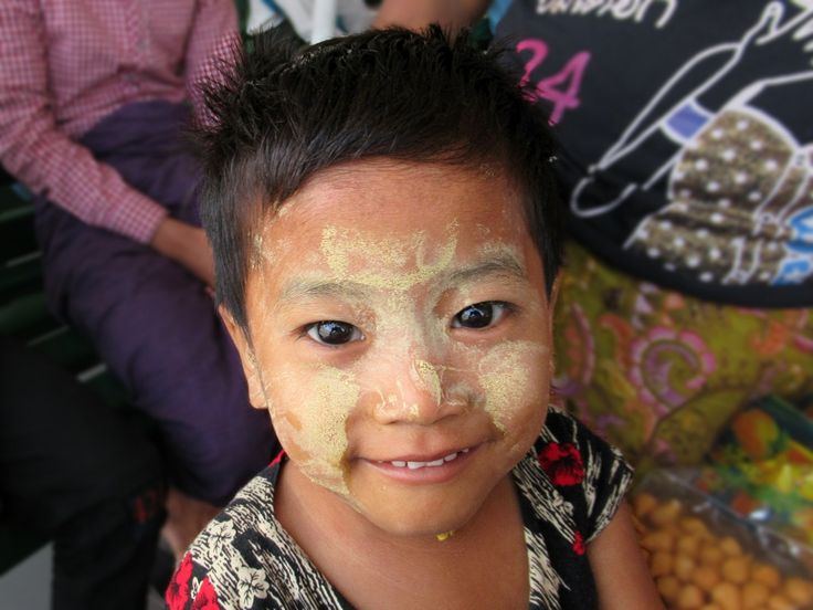 Thanaka paste covers the face of a child on a ferry at Yangon, Myanmar (Burma).