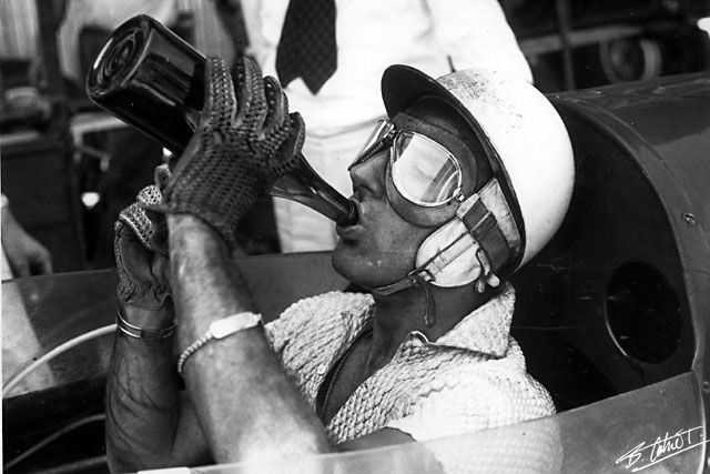 Sir Stirling Moss' iconic post-race champagne celebration after winning the 1957 Pescara Formula One Grand Prix in Italy. | Photo by Bernard Cahier