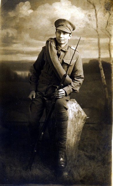 Early studio portrait of an Australian soldier. He wears the standard Great War uniform of the Australian Army, although he has a not often seen blanket roll over his shoulder. Affixed to his Lee Enfield (SMLE) is a nice hooked quillon bayonet, probably of Lithgow manufacture.