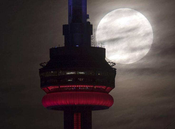 La Superluna dentras de la Torre CN de Toronto, Canadá.