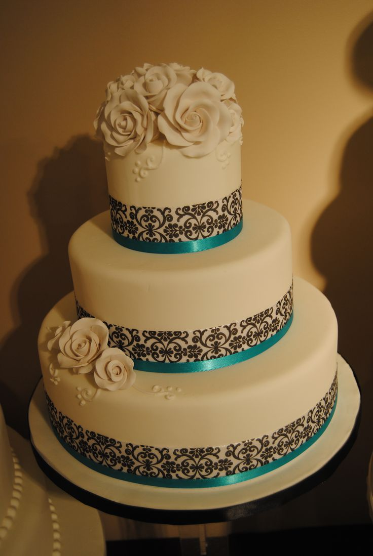 "Three tier fondant wedding cake with damask ribbon and roses. ""Pretty Sweet"" www.artisticcakedesign.ca #weddingcake #wedding #cake #damask #roses"