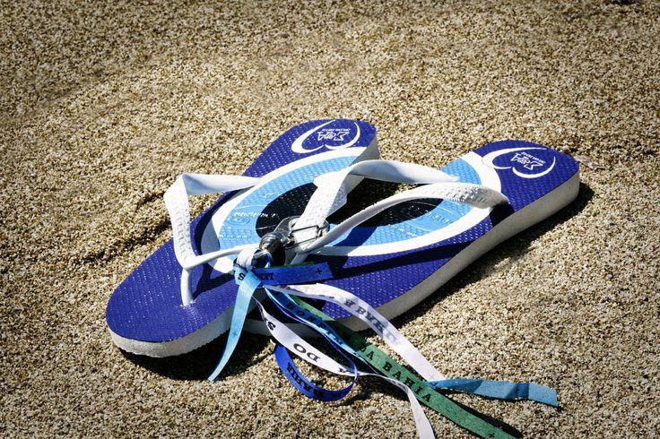"When Brazil Meets Greece Wedding @ Alemagou, Mykonos by De Plan V. Take of your heels and feel comfortable! Flip Flops, decorated with "" Bonfim da Bahia "", brazilian wish ribbons, bracelet! beach wedding party, couple monograms, mediterranean blue, sand!"