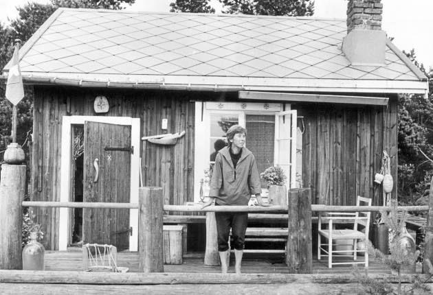 """Tove Jansson sommaren 1961 på verandan till ett av sina Muminhus, """"Vindrosens hus"""" som hon själv byggt på den lilla ön Bredskär i Finska viken."""