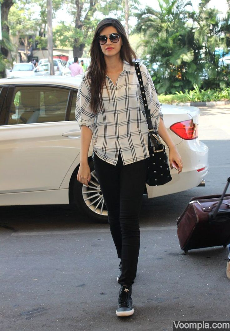 So pretty! Kriti Sanon leaves her long hair open as she takes a flight from Mumbai airport wearing black jeans, white shirt and large sunglasses. via Voompla.com