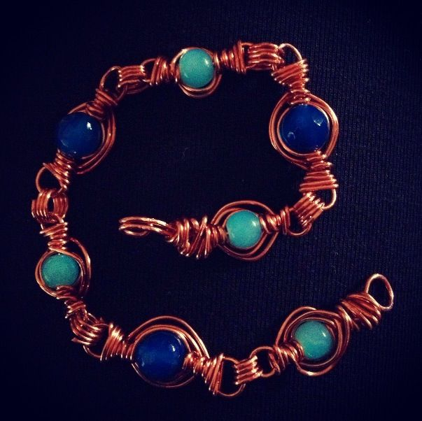 Braccialetto in rame con perle di vetro azzurre e blu.