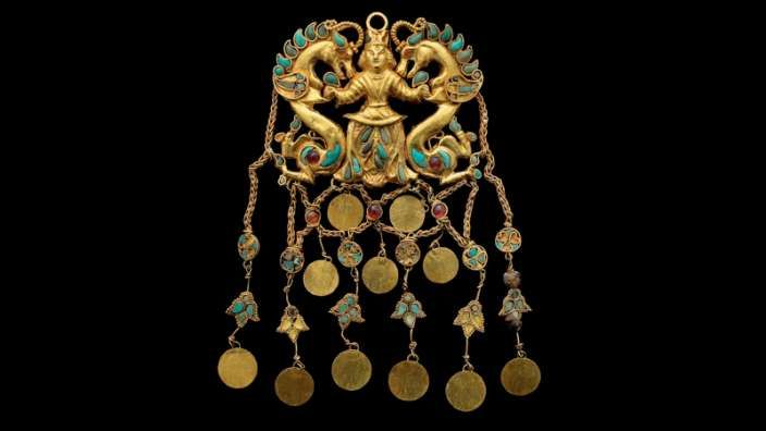 "PAIR OF PENDANTS DEPICTING THE ""DRAGON MASTER"", TILLYA TEPE. GOLD, TURQUOISE, GARNET, LAPIS LAZULI, CARNELIAN AND PEARL. 1ST CENTURY BC – 1ST CENTURY AD These elaborate hair ornaments depict a man wearing the tunic and fl owing pants typical of nomadic dress. He holds two dragon-like creatures by their forelegs, a mythic scene known from ancient Persian and Siberian art that suggests power and invincibility. Most unusually, these pendants are completely finished on both front and back."