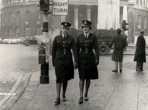 Two female police officers patrol on Oxford Street in central Manchester during the 1960s.  The building in the background is the famous Manchester Central Library.  The role of female officers changed slowly over time. At this time they formed the Women's Police Department and took on only a limited range of duties. http://www.gmpmuseum.com