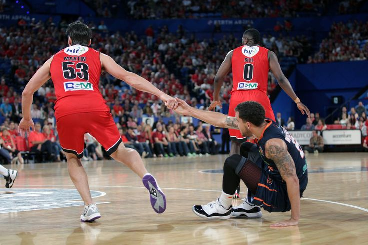 True sportsmanship. Captain Damian Martin helps up rival guard Scottie Wilbekin in the Wildcats clash with the Cairns Taipans. Photo: Tasha Hutchinson/Perth Wildcats