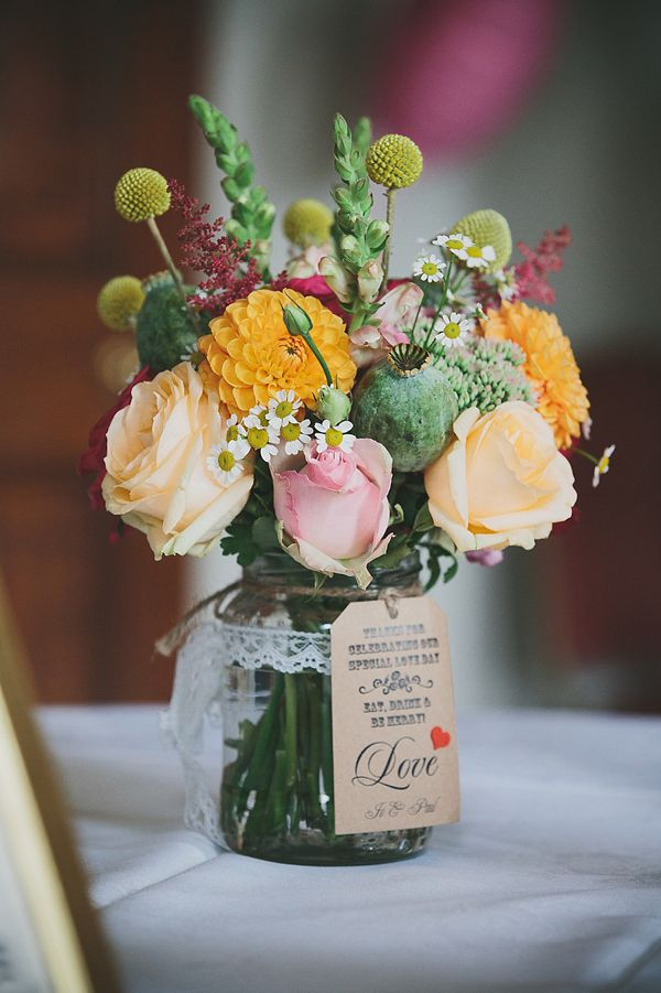 Peach and tangerine colour table centre piece florals in jam jars with lace.  From 'An Original 1950s Vintage Gold Wedding Dress For A Fun And Colourful Italian Inspired Wedding'.  http://www.mckinley-rodgers.com/