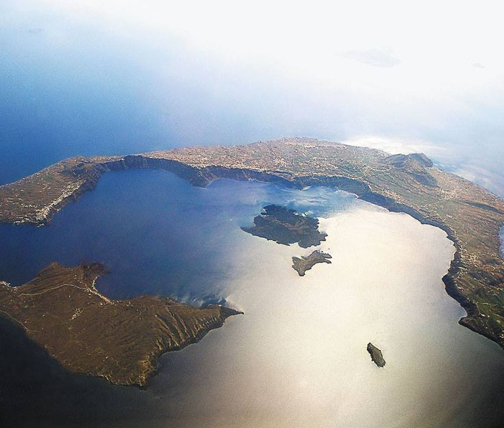 a great image of Santorini from above, you can clearly see the caldera formed after the massive volcanic eruption during the Bronze Age. Oia is visible on the top left rim of the caldera across from the island of Thirassia.  esperas-santorini.com   #santorini #oia