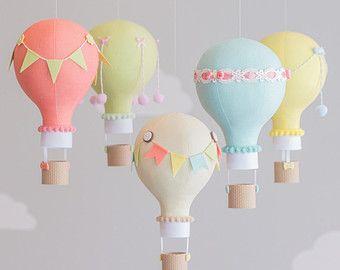 Blush rosado y gris bebé móvil en un tema de globo de aire caliente. Las fotografías muestran a 5 globos de aire caliente flotando las nubes puffy bajo dos. Cada globo es hecho a mano de varias telas coordinación y adornado con banderas diferentes del empavesado, panaderos de la guita, botones, pompones y canastitas, impresos con tecnología 3D, le dan un aspecto real de mimbre. Cuelgan de un móvil de madera con dos cadenas de banderas pequeñas del empavesado. Puede personalizar una de las…